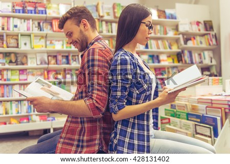 Handsome guy and attractive girl are reading books and smiling while sitting back to back in the book shop - stock photo
