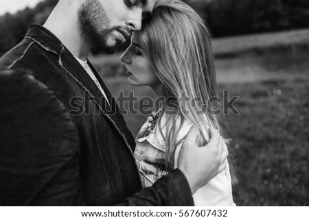 Handsome guy and blonde girl walking on the grass near the river and forest. man gently embraces girl, stroking his face and kisses