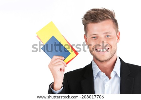 handsome guy closeup portrait and smiling. young man holding tickets on white background - stock photo