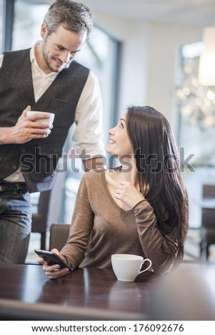 handsome guy dredge a young woman in a cafe - stock photo