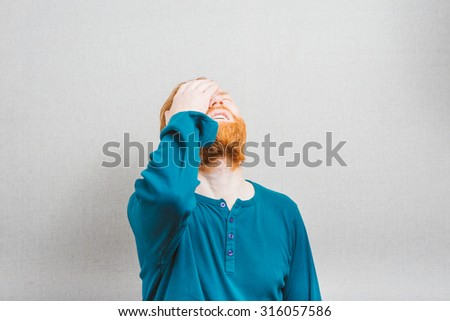Handsome guy has a terrible headache. He is touching his forehead with frustration and closing eyes. Isolated on grey background  - stock photo