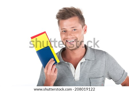 handsome guy holding passport and smiling. profile of man showing tickets on white background