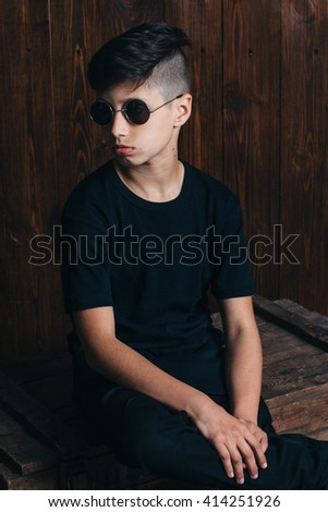 handsome guy in a black shirt and dark sunglasses on the background of wooden wall