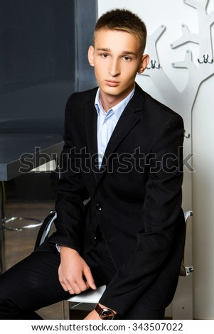 handsome guy in a black suit sitting in a restaurant - stock photo