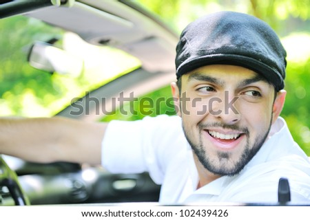 Handsome guy in a car smiling - stock photo