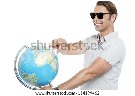 Handsome guy in goggles pointing at globe. Isolated on white background