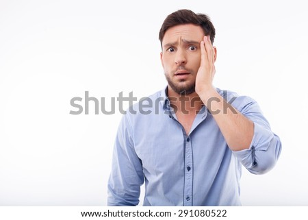 Handsome guy is looking the camera with horror in his eyes. He is puzzled and does not know what to do. He is touching his face with his hand. Isolated on a white background and there is copy space in - stock photo