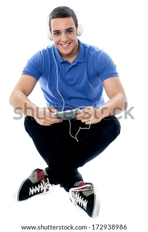 Handsome guy listening music from tablet pc device - stock photo