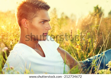 Handsome guy lying on the field. Young man enjoying nature outdoors.   - stock photo