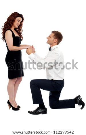 Handsome guy on knees proposing girl. Will you marry me? - stock photo