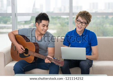 Handsome guy playing the guitar while his friend surfing the internet - stock photo