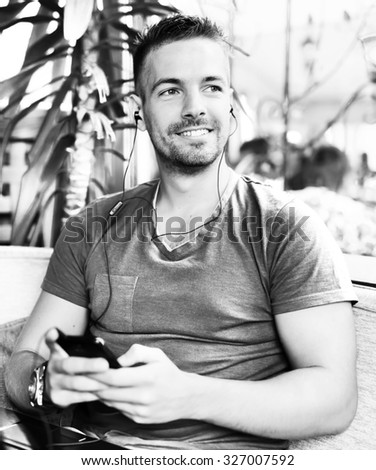 Handsome guy sitting at cafe bar, listening music and looking aside. He is holding mobile phone and smiling. Black and white photo with shallow depth of field.  - stock photo