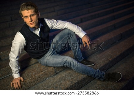 Handsome guy sitting on stairs. - stock photo