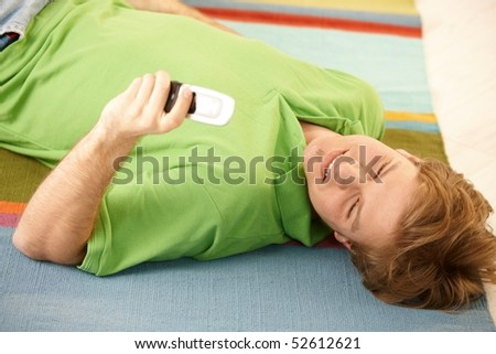Handsome guy using cellphone to write text message while lying on colorful carpet on back. - stock photo