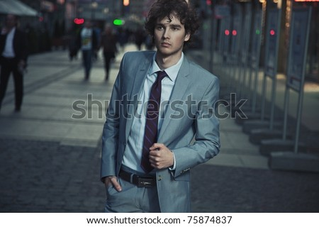 Handsome guy walking on a evening city street - stock photo