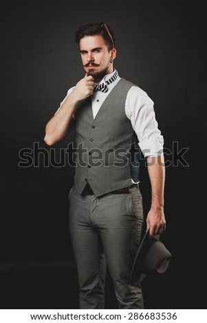 handsome guy with beard and mustache in suit on dark background in studio