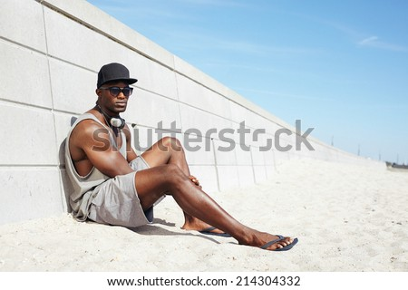 Handsome guy with headphones and sunglasses sitting on beach next to a wall. Muscular african american male model relaxing outdoors.  - stock photo