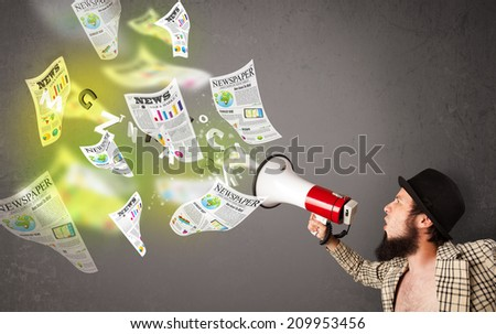 Handsome guy yelling into loudspeaker and newspapers fly out - stock photo