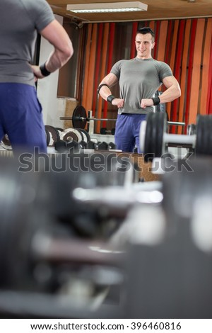 Handsome gym man lifting heavy free weights - stock photo