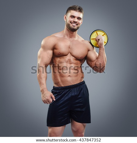 Handsome gym trainer guy isolated on grey background. Muscular sportsman with perfect abs smiling - stock photo