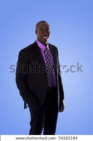 Handsome happy African American corporate business man smiling, wearing black suit with purple shirt, standing with hand in pocket,  isolated. - stock photo