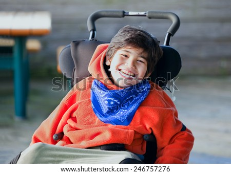 Handsome, happy biracial eight year old boy smiling in wheelchair outdoors - stock photo