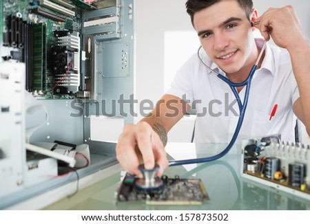 Handsome happy computer engineer holding stethoscope in bright office