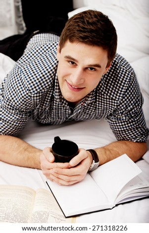Handsome happy man with a book in his bed. - stock photo