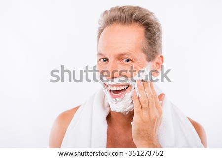 Handsome happy man with towel smearing shaving foam on his chin