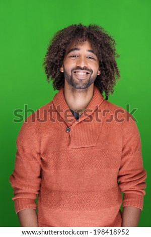 Handsome happy modern African American man with a wild curly afro hairstyle standing smiling against a green background - stock photo