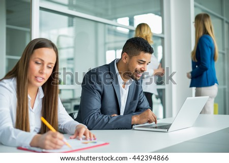 Handsome happy young businessman working on his laptop - stock photo