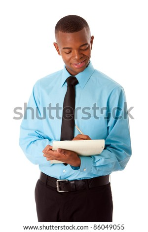 Handsome happy young male corporate MBA business student in blue shirt and black tie writing ideas notes on notepad, isolated.