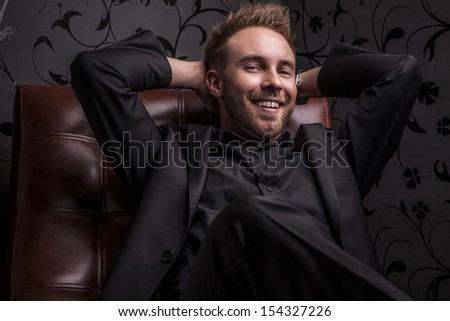 Handsome happy young man in dark suit relaxing on luxury sofa. - stock photo