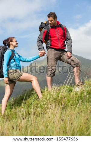 Handsome hiker helping his girlfriend uphill in the countryside - stock photo