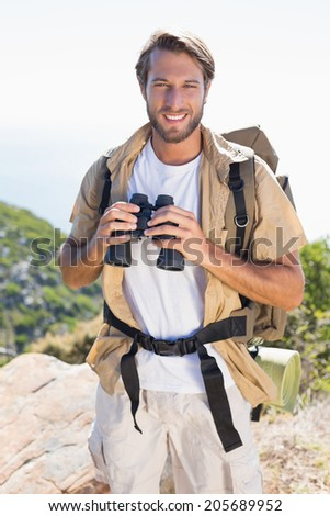 Handsome hiker holding binoculars on mountain trail on a sunny day - stock photo