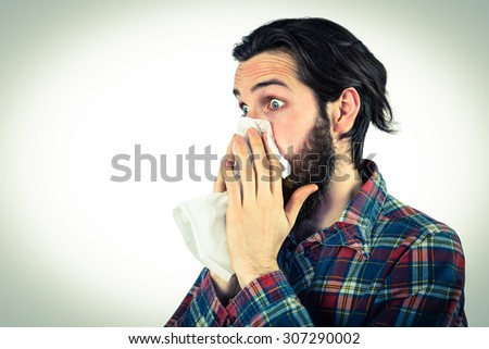 Handsome hipster blowing his nose on vignette background - stock photo