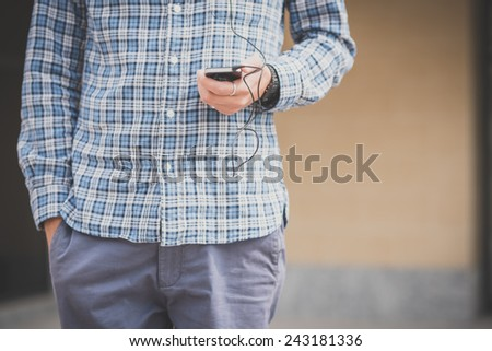 handsome hipster casual multitasking modern man listening music and using smartphone in the city - stock photo
