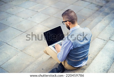Handsome hipster modern businessman using laptop in the city - stock photo