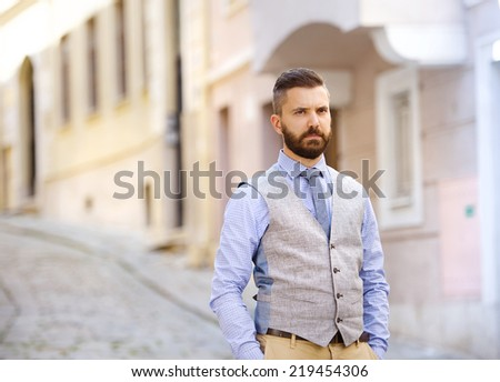 Handsome hipster modern businessman with beard walking in town - stock photo