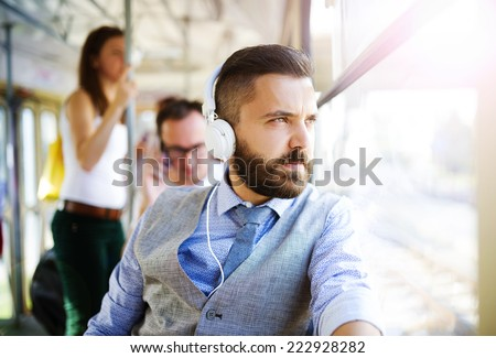 Handsome hipster modern man with headphones traveling by tram in town - stock photo