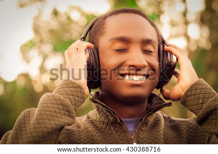 Handsome hispanic black man wearing green sweater in outdoors park area, hands holding headphones covering ears and smiling enjoying some music - stock photo