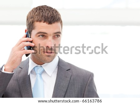Handsome hispanic businessman on the phone standing in the hall of his building - stock photo