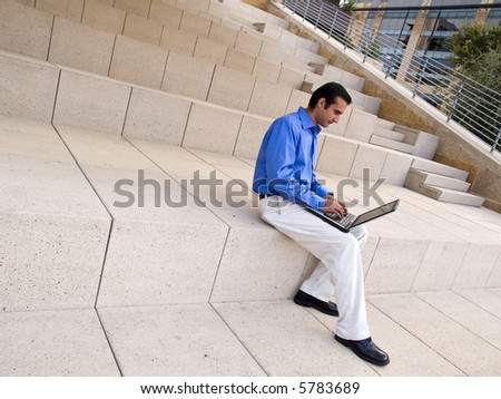 Handsome hispanic businessman surfing the internet on a laptop whle sitting on steps outside an office building.