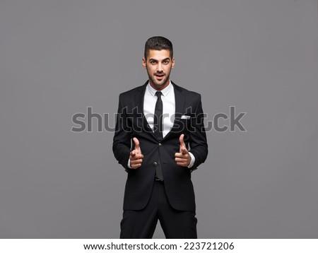 handsome hispanic elegant man in black suit on grey background - stock photo