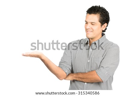 Handsome hispanic man wearing button dress shirt casual clothes looking down at hand displaying imaginary product on flat open empty palm suitable for item placement. Half Horizontal - stock photo