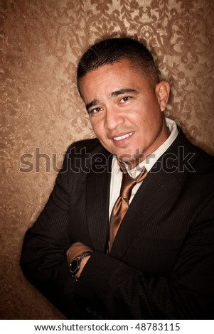 handsome Hispanic Man with Arms Crossed on Gold background - stock photo