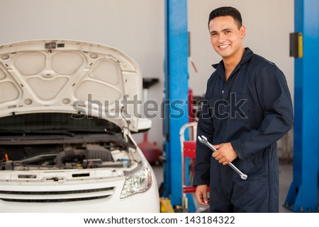 Handsome Hispanic mechanic enjoying his work at an auto shop and smiling