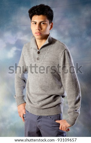 Handsome Hispanic young man standing with his hands in his pockets and eye contact