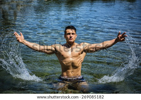 Handsome, hot young bodybuilder in the sea, splashing water up, showing his muscular torso and arms - stock photo