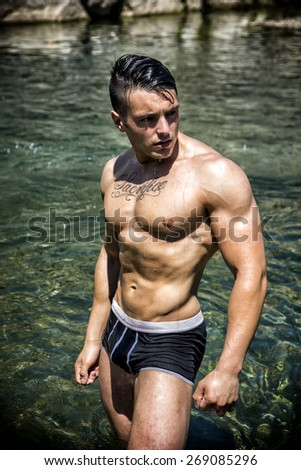 Handsome, hot young bodybuilder shirtless in trunks, in the sea showing his muscular torso and arms - stock photo